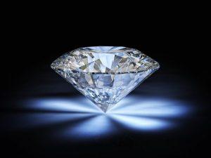 Photo d'un diamant taillé en pointe sur fond noir avec reflets